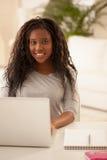 Adolescente africano sorridente che per mezzo del computer portatile a casa Fotografia Stock