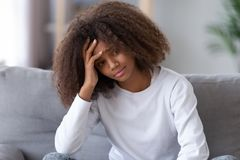 Adolescente afro-americano infeliz que senta-se apenas, tendo o problema fotografia de stock