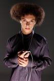 Adolescente afro espeso grande del pelo que escucha la música Fotografía de archivo