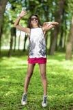 Adolescente afroamericano activo con los Dreadlocks que hacen un salto de altura con las manos extendidas Fotos de archivo