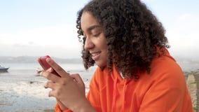 Adolescente afroamericano Biracial de la muchacha en un frente de mar usando su teléfono celular elegante para los medios o manda almacen de metraje de vídeo