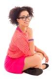Adolescente afroamericano bonito en la sentada rosada aislado encendido Imágenes de archivo libres de regalías