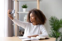 Adolescente afroamericano che prende selfie durante la preparazione di compito fotografie stock