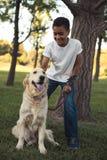 Adolescente afroamericano con el perro Foto de archivo