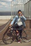 Adolescente afroamericano con la bebida de consumición de la bicicleta en parque del monopatín Imágenes de archivo libres de regalías