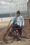 Adolescente afroamericano con la bicicleta en parque del monopatín Imagen de archivo