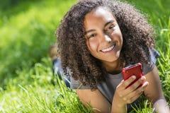 Adolescente afroamericano de la muchacha de la raza mixta en el teléfono celular Foto de archivo libre de regalías