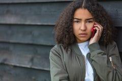 Adolescente afroamericano de la muchacha de la raza mixta en el teléfono celular Fotografía de archivo