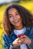 Adolescente afroamericano de la muchacha de la raza mixta en el teléfono celular Imagen de archivo