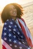 Adolescente afroamericano de la muchacha de la raza mixta envuelto en bandera de los E.E.U.U. Foto de archivo libre de regalías