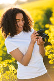 Adolescente afroamericano de la muchacha de la raza mixta hermosa que usa la cámara Foto de archivo