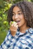 Adolescente afroamericano de la muchacha de la raza mixta que come Apple Imágenes de archivo libres de regalías
