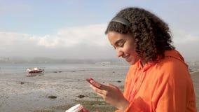 Adolescente afroamericano de la muchacha de la raza mixta biracial hermosa por el café de consumición del mar que escucha la músi almacen de metraje de vídeo