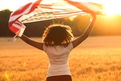 Adolescente afroamericano de la muchacha de la raza mixta con la bandera de los E.E.U.U. en la puesta del sol Foto de archivo