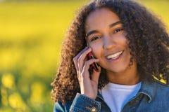 Adolescente afroamericano de la muchacha de la raza mixta que habla en el teléfono celular Imagen de archivo libre de regalías