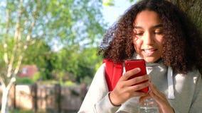 Adolescente afroamericano de la muchacha de la raza mixta que se inclina contra un árbol usando una cámara del teléfono celular p almacen de metraje de vídeo