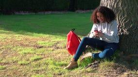 Adolescente afroamericano della ragazza della corsa mista che per mezzo del telefono da un albero archivi video