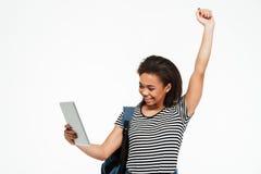 Adolescente afroamericano feliz con la mochila que sostiene la PC Fotografía de archivo libre de regalías