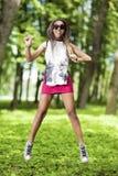 Adolescente afroamericano feliz con los Dreadlocks que hacen un salto de altura Imagenes de archivo