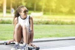 Adolescente afroamericano feliz positivo del retrato con los Dreadlocks que presentan en Longboard en área del parque Fotografía de archivo libre de regalías