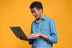 Adolescente afroamericano feliz que trabaja con el ordenador portátil Foto de archivo libre de regalías