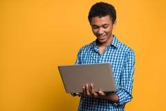 Adolescente afroamericano feliz que trabaja con el ordenador portátil Fotos de archivo libres de regalías