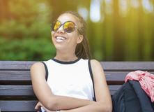 Adolescente afroamericano feliz y sonriente con los Dreadlocks largos que presentan en parque al aire libre en gafas de sol Fotografía de archivo