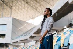 Adolescente afroamericano hermoso con los auriculares que mira el partido en el estadio Imagen de archivo