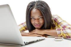 Adolescente afroamericano joven hermoso con el ordenador portátil Fotos de archivo