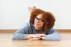Adolescente afroamericano negro que se acuesta en el piso de madera Imágenes de archivo libres de regalías