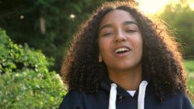 Adolescente afroamericano o giovane donna della ragazza della corsa mista che ride, sorridente e soffiante un dandelio stock footage