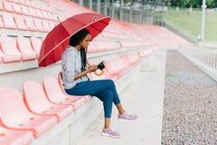 Adolescente afroamericano pensativo debajo del paraguas rojo Ella está charlando vía el teléfono móvil Vista lateral Foto de archivo