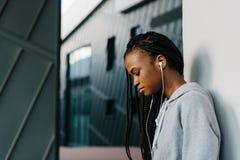 Adolescente afroamericano pensativo en los auriculares que se inclinan en la pared Retrato lateral al aire libre Fotos de archivo