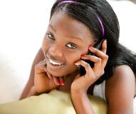 Adolescente afroamericano que brilla intensamente que habla en el teléfono Foto de archivo libre de regalías