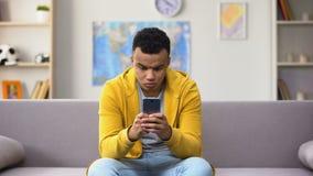 Adolescente afroamericano que juega al juego viral en el smartphone, apego del artilugio metrajes