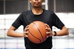 Adolescente afroamericano que lleva a cabo un baloncesto en la corte Fotos de archivo libres de regalías