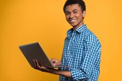 Adolescente afroamericano que trabaja con el ordenador portátil Fotos de archivo
