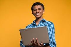 Adolescente afroamericano que trabaja con el ordenador portátil Fotografía de archivo libre de regalías