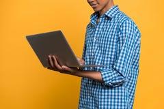 Adolescente afroamericano que trabaja con el ordenador portátil Foto de archivo libre de regalías