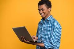 Adolescente afroamericano que trabaja con el ordenador portátil Imagen de archivo libre de regalías