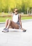 Adolescente afroamericano sonriente con el tablero largo que presenta en parque al aire libre en gafas de sol Imagen de archivo libre de regalías