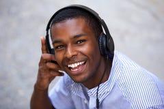 Adolescente afroamericano sonriente con los auriculares Imagenes de archivo