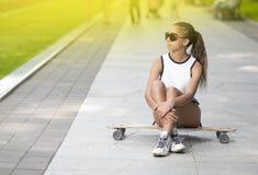 Adolescente afroamericano sonriente feliz con el tablero largo que presenta en parque Foto de archivo libre de regalías