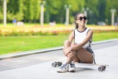 Adolescente afroamericano sonriente feliz con el tablero largo que presenta en parque al aire libre Fotografía de archivo