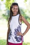 Adolescente afroamericano sonriente feliz en la ropa informal que presenta afuera en parque Fotos de archivo