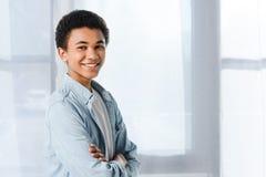 adolescente afroamericano sonriente que se coloca con los brazos cruzados y la mirada de la cámara Foto de archivo libre de regalías