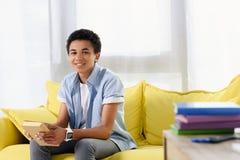 adolescente afroamericano sonriente que se sienta con el libro en el sofá Foto de archivo libre de regalías