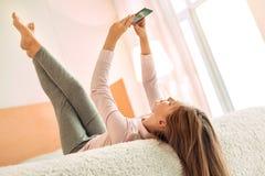 Adolescente agréable se trouvant sur le lit et textoter Image stock