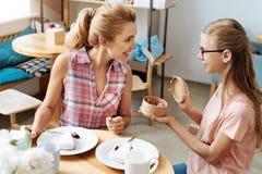Adolescente agradable asombrosamente su madre con los macarons Imagen de archivo