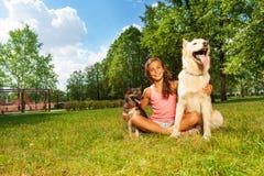 Adolescente agradable con sus perros en el césped del parque Fotos de archivo